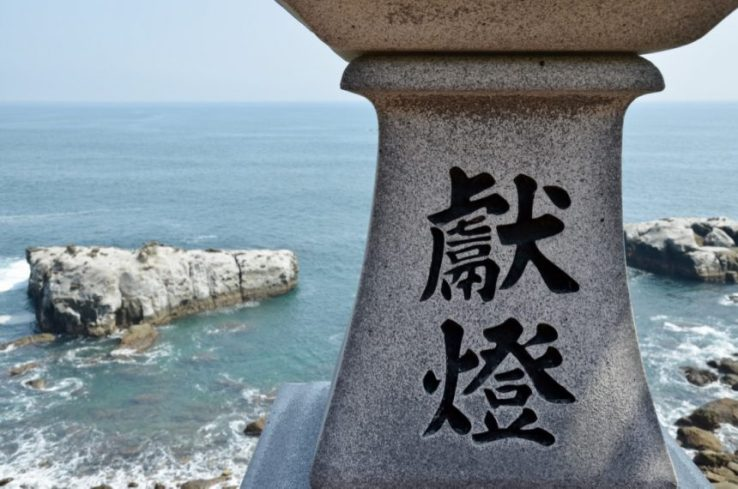 Inseguendo i sakura: nel complesso del santuario di Udo Jingū, il particolare del fusto di una laterna con sopra stampati ideogrammi e con sfondo di Oceano Pacifico e scogli